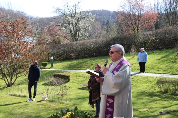 Man sieht einen Pfarrer der auf einer Wiese steht und seinen Gottesdienst an der frischen Luft abhält.