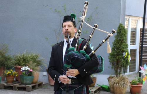 Man sieht einen Dudelsackspieler mit typisch schottischer Kleidung an. Er läuft auf einem gepflasterten Weg. Sein Dudelsack ist schwarz/grün.