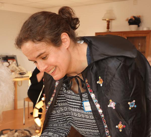 Auf dem Bild sehen wir eine Betreuerin, die einen schwarzen Zauberumhang trägt, wie sie Würmer aus Garn an die Bewohner verteilt.