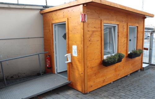 Man sieht eine braune Holzhütte mit zwei weißen Fenstern an denen jeweils ein Blumenkasten befestigt ist.