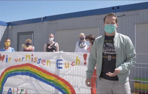 Man sieht einen Mann vor einem Zaun stehen. An dem Zaun hängt ein Banner bzw. Plakat mit der Aufschrift 'Wir vermissen euch!' in Regenbogenfarben und mit einem Regenbogen darunter. Alle Personen die man sieht, tragen eine Mund-Nasen-Schutz und halten Abstand. Hinter dem Zaun stehen fünf Frauen.
