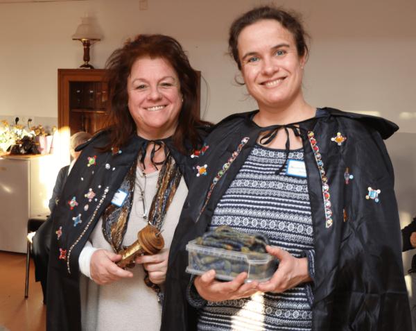 Man sieht zwei Betreuerinnen, die schwarze Zauberumhänge tragen, sie halten eine Spindel und eine Kiste voll Garnwürmer in den Händen.